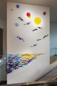 abstract wall sculpture of birds, sun and water